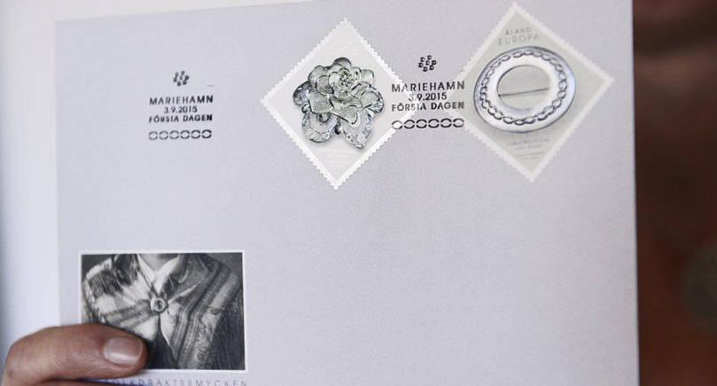 FRIMÄRKE Det schweiziska frimärket till vänster och det åländska till höger. Båda två är designade av åländska Cecilia Mattsson. Det schweiziska frimärket visar en folkdräktsbrosch som tillhör den kvinnliga folkdräkten för kantonen Bern. Det åländska frimärket visar Ålandsspännet som används för att fästa axelduken. Tanken är att frimärkena ska fästas på snedden, som på bilden.
